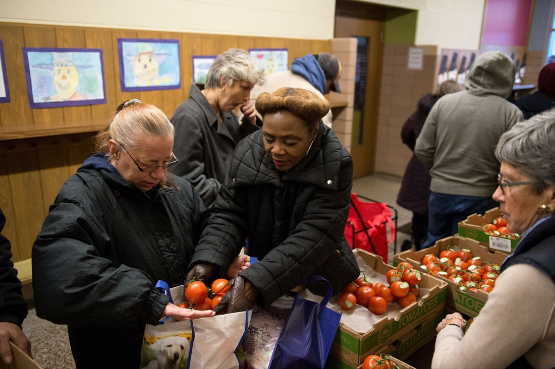food bank volunteer helping client choose tomatoes